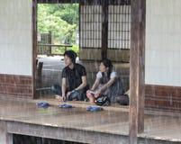 Ett ungt japanskt par ser regnet från tempelbuildien Arkivbilder