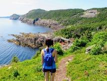Ett ungt kvinnligt fotvandrareanseende ovanför Atlanticet Ocean som förbiser den ojämna kusten av Newfoundland och labradoren, Ka royaltyfri foto