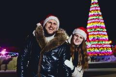 Ett ungt le lyckligt gift par i det röda locket på jul utomhus fotografering för bildbyråer
