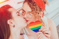 Ett ungt lesbiskt par som kysser och rymmer en hjärta med flaggan arkivbild