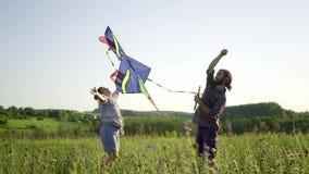 Ett ungt lyckligt älska parflyg en drake i ett sommarfält arkivfilmer