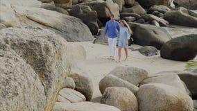 Ett ungt lyckligt härligt par av vänner, i blå kläder rymmer händer och att promenera kusten som ler stock video