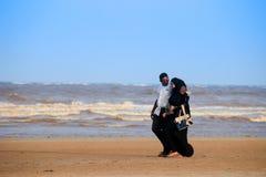 Ett ungt lyckligt muslimskt svart par promenerar kusten av Indiska oceanen royaltyfri bild