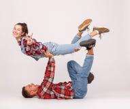 Ett ungt lyckligt par som gör akrobatiska jippon bakgrund isolerad white royaltyfri fotografi
