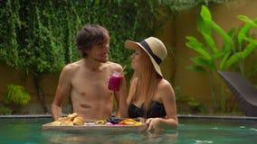 Ett ungt par av bröllopsresaturister har deras egen personliga frukost på en sväva tabell i en privat simbassäng stock video