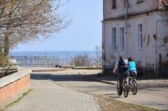 Ett ungt par av cyklister rider till och med tomma gator under klart väder Grabben och flickan går på cykeln royaltyfria foton