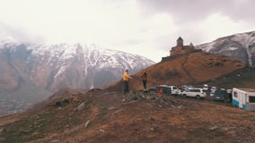 Ett ungt par av handelsresande lyfter hans armar i bakgrunden av berg lager videofilmer