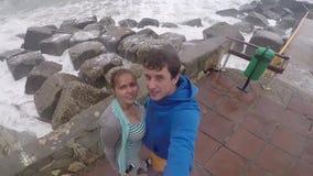 Ett ungt par, en man och en kvinna står på pir och gör selfie på stranden, vågor bryter mot stora stenar långsamt lager videofilmer