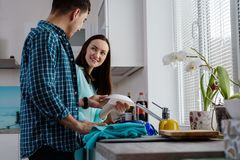 Ett ungt par i köket tillsammans som tvättar och som torkar disken, en nedersta sikt och en sidosikt, glädjen av familjeliv Arkivbild