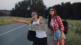 Ett ungt par liftar anseende på vägen En man och en kvinna att stoppa bilen på huvudvägen med ett tecken Adrenture lager videofilmer