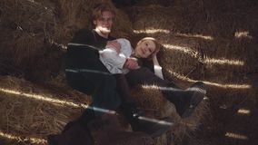 Ett ungt par ligger krama hö i ladugården Den lyckliga le pojken och flickan spenderar tid tillsammans långsam rörelse arkivfilmer