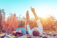 Ett ungt par, mankvinna, i sommar för vetefält, lögn på filten Handgester indikerar stjärnor Begreppsförälskelse, datum, sinnesrö royaltyfria bilder