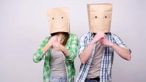 Ett ungt par med pappers- påsar på deras huvud är lyckligt och dansen stock video