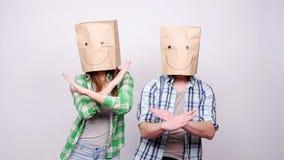 Ett ungt par med pappers- påsar på deras huvud är lyckligt och dansen arkivfilmer
