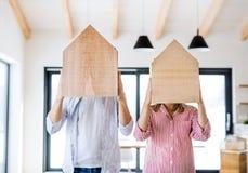 Ett ungt par med trähus, ett nytt hem- begrepp för inflyttning arkivfoto