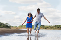 Ett ungt par promenerar stranden royaltyfri fotografi