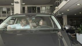 Ett ungt par sitter i kabin för bil` s i visningslokal arkivfilmer