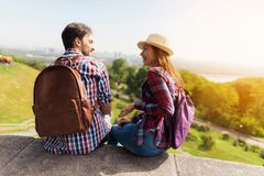 Ett ungt par sitter på en balustrad Grabben och flickan ser de och ler Royaltyfri Fotografi