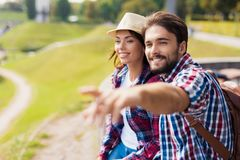 Ett ungt par sitter på en balustrad Grabben visar hans finger någonstans i avståndet Fotografering för Bildbyråer