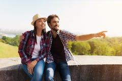 Ett ungt par sitter på en balustrad Grabben visar hans finger någonstans i avståndet Royaltyfri Fotografi