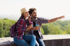 Ett ungt par sitter på en balustrad Grabben visar hans finger någonstans i avståndet Arkivbild