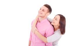 Ett ungt par som tillsammans står, kramar och ser somethi Arkivfoton