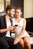 Ett ungt par som tycker om ett exponeringsglas av vin i ett asiatiskt stilhotell r Arkivfoton