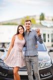 Ett ungt par står nära deras nya använda bil Arkivfoton