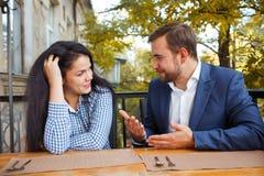 Ett ungt par talar i ett kafé utomhus arkivfoton