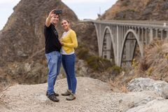 Ett ungt par tar en selfie i fron av den stora liten vikbron, Big Sur, Kalifornien, USA arkivbilder
