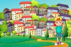 Ett ungt pojkeanseende på bergstoppet över byn Royaltyfria Bilder