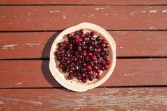 Ett uppläggningsfat av körsbär på en lantlig picknicktabell arkivfoto