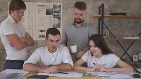 Ett vänligt lag av kontorsarbetare diskuterar tillsammans en teckning, stopptid stock video