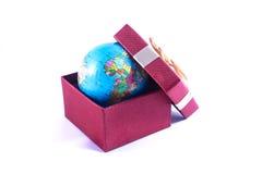 Ett världsjordklot i en gåvaask arkivfoton