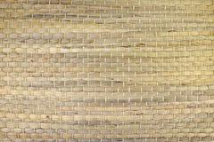 Ett vävt mattt av vasser eller sugrör-guling i färg Texturen av den torra rottingen arkivfoto