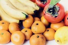 Ett val av ordnade olika nya frukter av bananer, mandariner, persimoner och citroner på det vita bakgrundsslutet upp arkivfoto