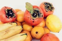 Ett val av ordnade olika nya frukter av bananer, mandariner, persimoner och citroner på det vita bakgrundsslutet upp arkivfoton