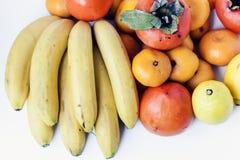 Ett val av ordnade olika nya frukter av bananer, mandariner, persimoner och citroner på det vita bakgrundsslutet upp royaltyfria bilder