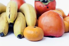 Ett val av ordnade olika nya frukter av bananer, mandariner, persimoner och citroner på det vita bakgrundsslutet upp royaltyfri foto