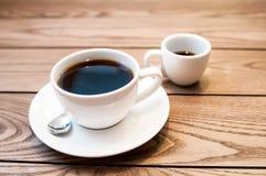 Ett varmt americanokaffe för kopp på den wood tabellen Arkivfoto