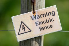 Ett varnande folk för krokigt tecken att ett elektriskt staket är närvarande Tecknet fästas till ett trådstaket med en grön arkivbilder