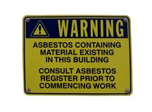 Ett varningstecken på en byggnad som råder att material innehåller asbest fotografering för bildbyråer
