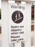 Ett varningstecken som säger trappa, är halt, när det är vått, behar tar c Royaltyfri Bild