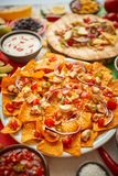 Ett ?ver huvudet foto av ett sortiment av m?nga olika mexicanska foods p? en tabell royaltyfria bilder
