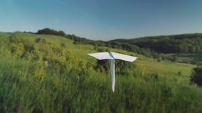 Ett verkligt pappers- flygplan flyger över en pittoresk dal Pov-skott royaltyfria foton