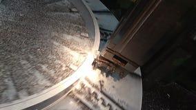 Ett videogem som skäraren i hjälpmedelhållaren av drejbänken med belysning bearbetar i en titandetalj av en roterande platta arkivfilmer