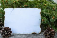Ett vitt ark av papper som br?nns l?ngs kanterna och de gr?na filialerna av en julgran p? bakgrunden av gamla tr?br?den arkivfoton