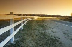 Ett vitt staket följer banan av rutt 33 nära Ojai in i solnedgången Royaltyfri Foto