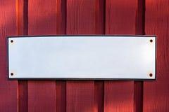 Ett vitt tomt tomt ståltecken med kopieringsutrymme på en röd träladugårdvägg arkivfoton