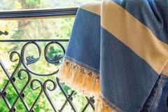 Ett vitt turkiskt peshtemal för beiga och för blått/handduk på räcke för en smidesjärn med den oskarpa naturen i bakgrunden royaltyfria bilder